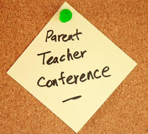 post-it note pinned on bulletin board with words parent teacher conferences